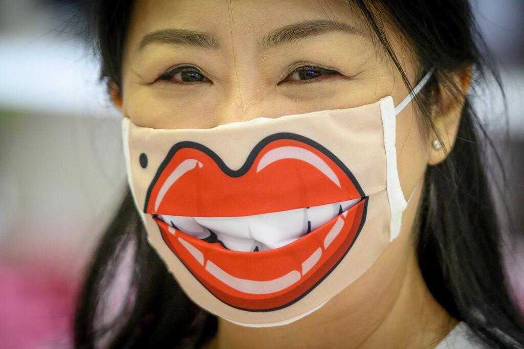 امرأة ترتدي قناع وجه مبتسم في مركز تجاري في بانكوك