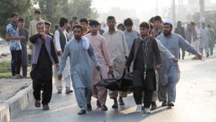 رجال ينقلون أحد ضحايا الانفجار في كابول