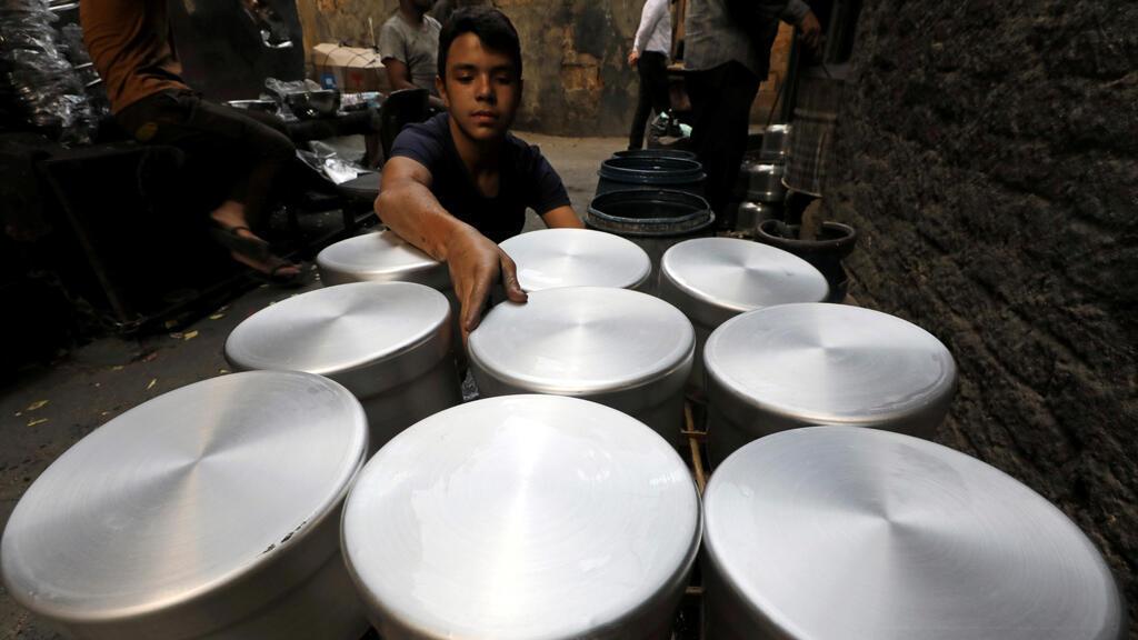 طفل يرتب أدوات طهي الألمنيوم في ورشة عمل بالقاهرة-