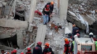 عمال الانقاذ يبحثون في موقع مبنى انهار، بعد زلزال في العزيج-