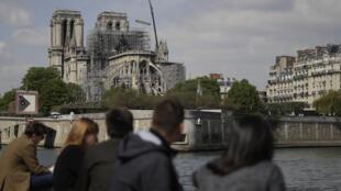 يجلس الناس على ضفاف نهر السين أمام كاتدرائية نوتردام في باريس في 17 أبريل 2019 بعد يومين من الحريق الذي دمر المبنى في وسط العاصمة الفرنسية.