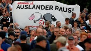 """متظاهرون يرفعون لافتة كتب عليها """"المجرمون الأجانب إلى الخارج!"""" في كيمنتس"""