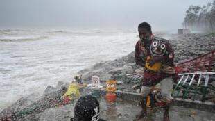 كاهن هندوسي بالقرب من معبد على الواجهة البحرية بينما تضرب الرياح العاتية منطقة بالاسور في ولاية أوديشا في 26 مايو 2021 حيث يتجه إعصار ياس نحو الساحل الشرقي للهند في خليج البنغال.