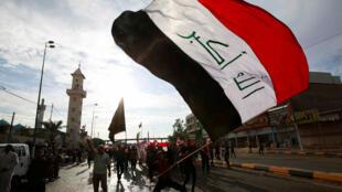 المتظاهرون يحملون العلم العراقي وهم يتجمعون خلال احتجاج في النجف-